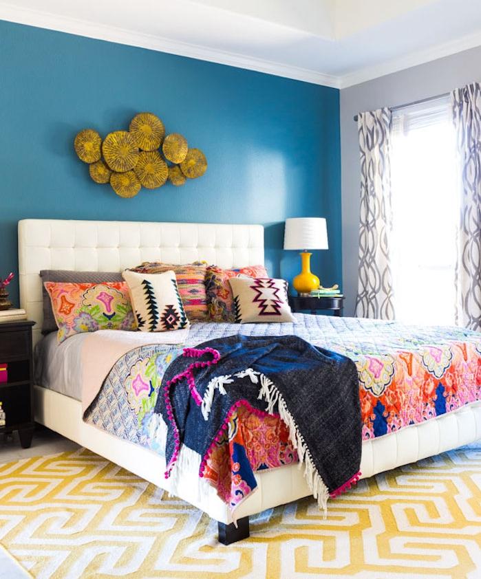 deco chambre parentale avec pan de mur bleu, linge de lit coloré aa motifs floraux, style boheme chic, tapis blanc et jaune
