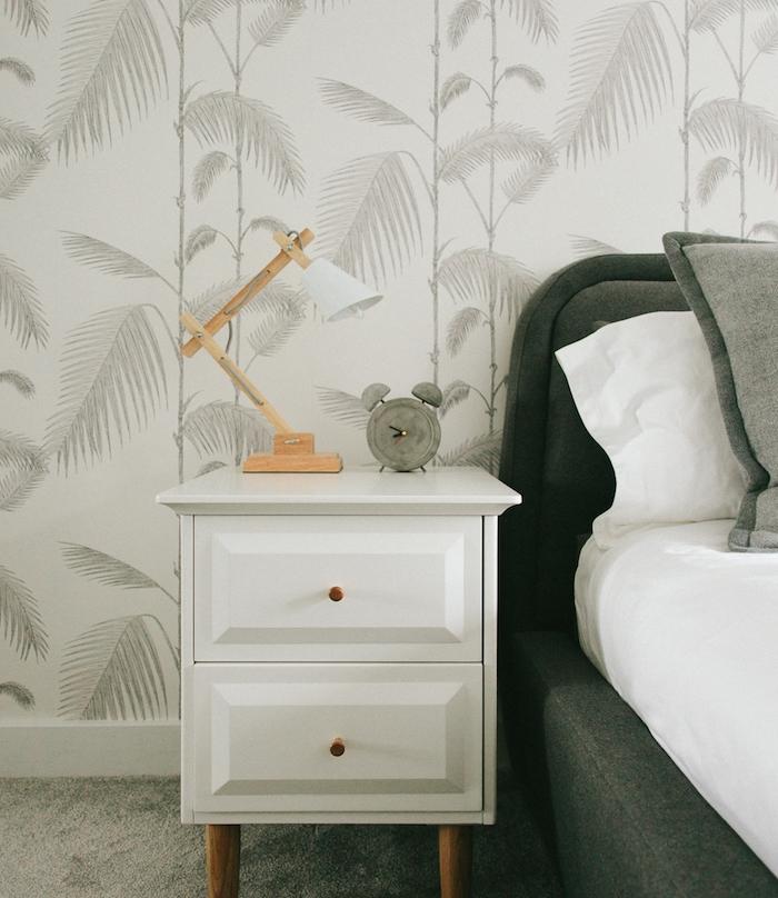 décoration chambre adulte, tapisserie murale tropical, greenery, palmiers gris graphiques sur un fond blanc, lit gris et linge blanc, réveil béton, lampe design original