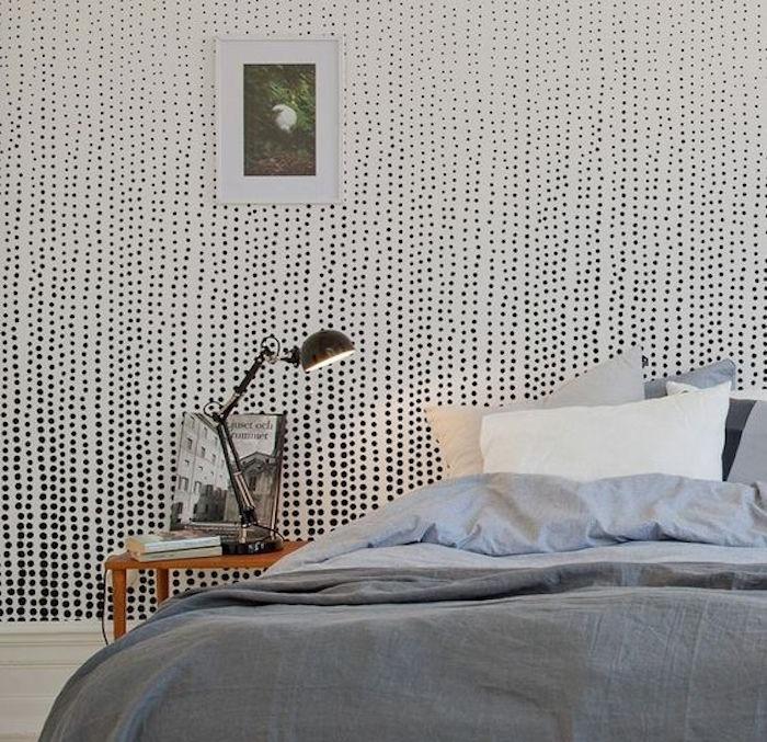 exemple de papier peint scandinave intéressant, mur blanc décoré à pois noirs, linge de lit blanc et gris, table de nuit bois