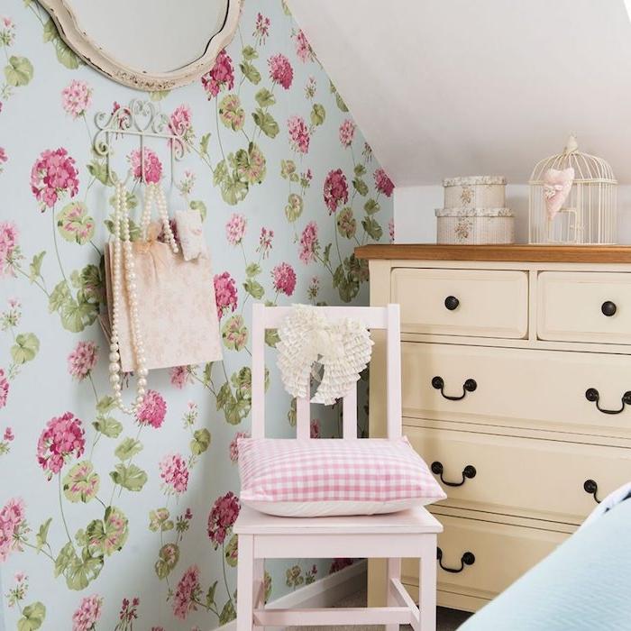 deco chambre adulte style campagne chic, tapisserie chambre florale, fleurs rose sur un fond bleu, commode beige, chaise vintage rose, cage oiseau decoration