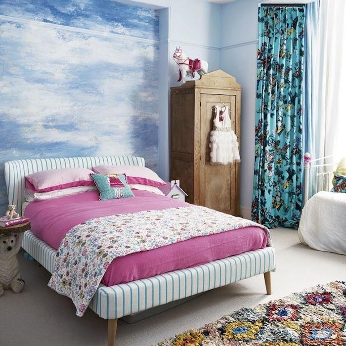 papier peint enfant pour décorer une chambre fille, imprimé artistique, nuage bleue et blanc, lint blanc à rayures bleues, matelas rose, couverture florale, rideaux coloré et armoire vintage bois brut
