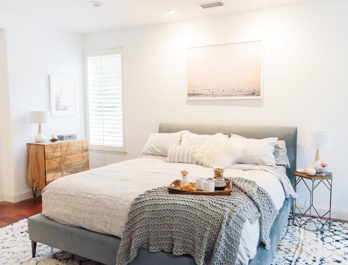 chambre gris et blanc, peinture murale blanche et linge blanc sur un lit gris, tapis à motifs geometriques, commode bois, parquet marron et table de nuit metallique