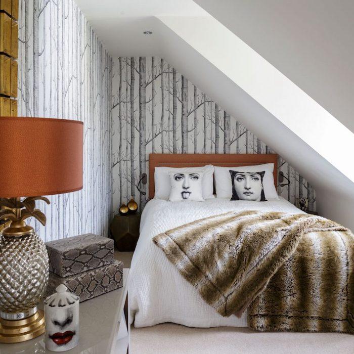 exemple de deco chambre sous pente, mur décoré de papier peint scandinave, lit bois avec linge blanc, couverture fausse fourrure, boîtes rangement imprimé serpent