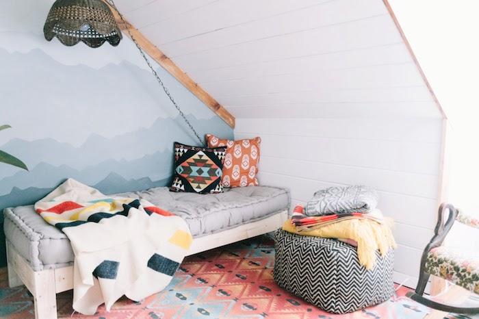 idee deco chambre sous pente, pan de mur décoré de papier peint effet ombré, dessin artistique bleu, lit bois blanc, matelas gris, tapis oriental à motifs géométriques, coussins colorés, suspension noire originale