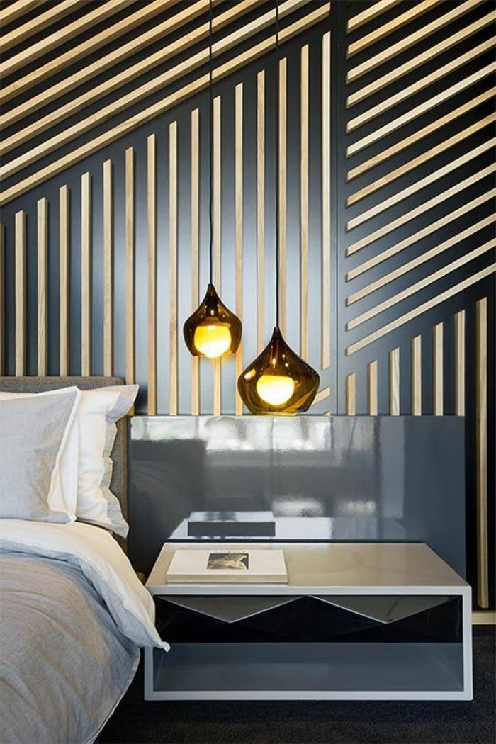 décoration chambre adute avec mur en noir décoré de motifs graphiques en bois clair avec meuble lit bas aux tiroirs noirs