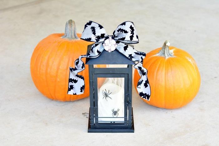 lanterne noir avec ruban noir et blanc et araignées artificielles, citrouilles orange, activité manuelle halloween facile