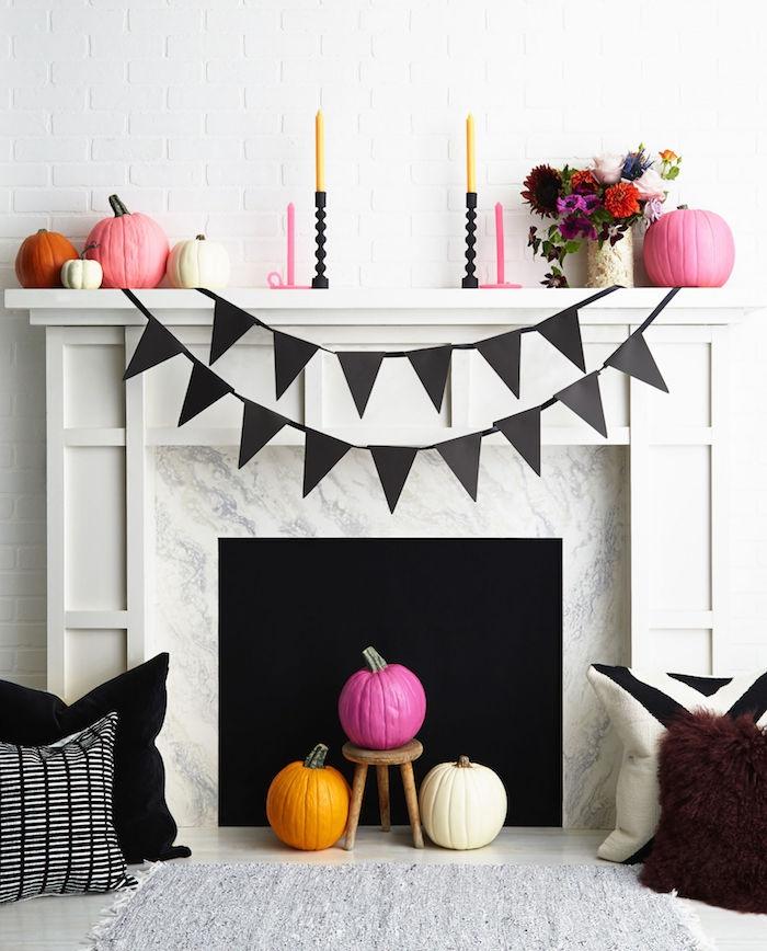 deco halloween a faire soi meme, citrouilles colorées en orange, rose et blanc, guirlande a fanions, bouquet de fleurs automnales, bougeoirs modernes, decoration cheminée
