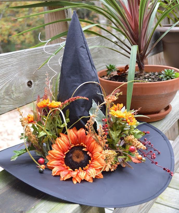 un chapeau de sorcière noir avec decoration de fleurs, sur un banc en bois, deco halloween a faire soi meme