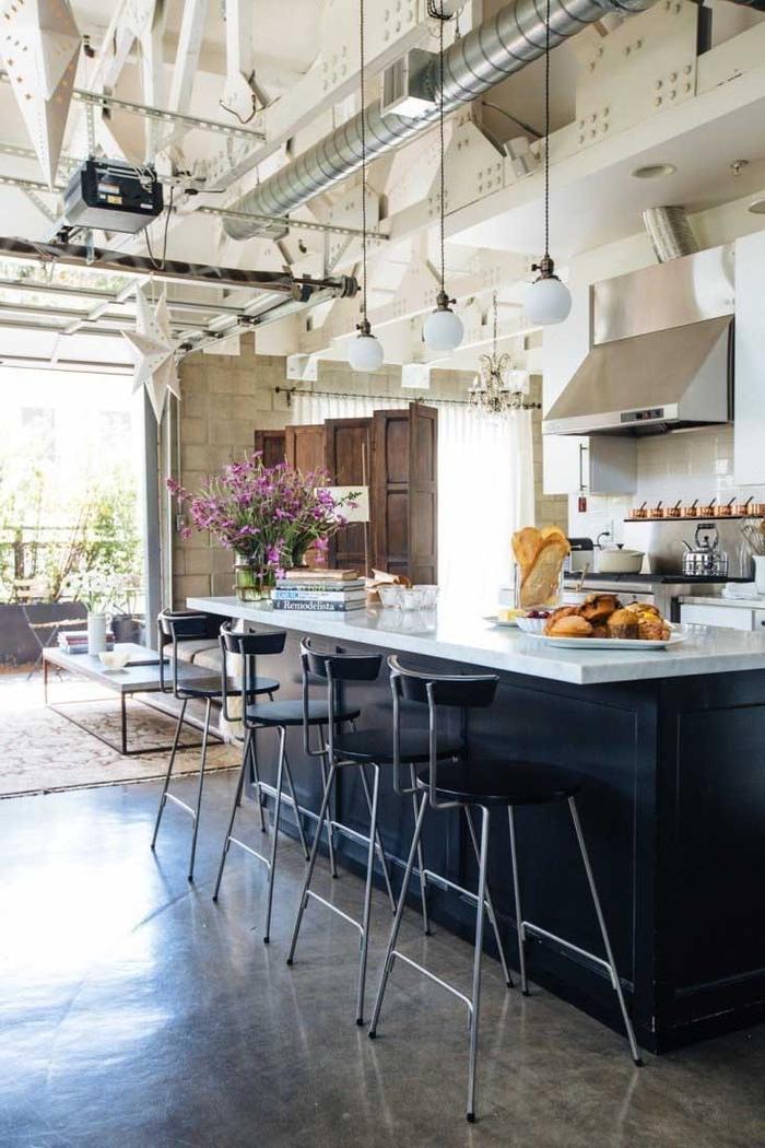 cuisine d'ambiance loft industriel aux structures fonctionnelles apparentes et un îlot central au design chic