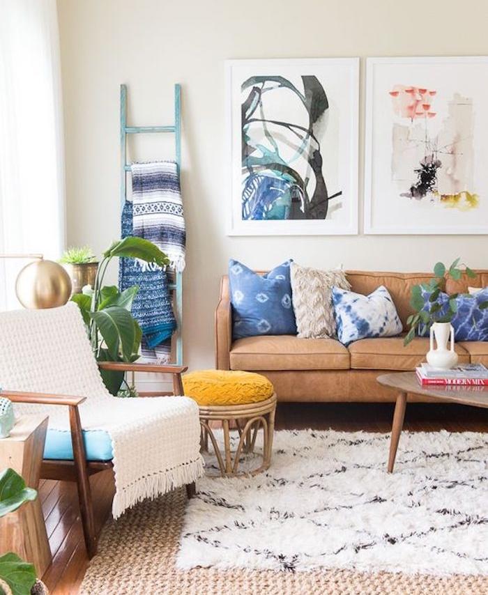salon style boheme scandinave, canapé marron, tapis moelleux, table, tabouret et chaise en bois, echelle deco bois, repeinte en bleu, rangement de couvertures