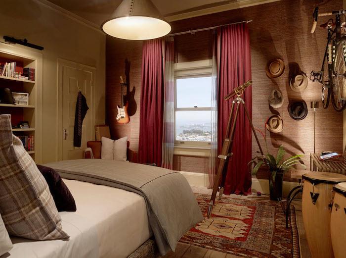 chambre ado garçon, papier peint à nuance marron, grande fenêtre avec rideaux longs et rouges