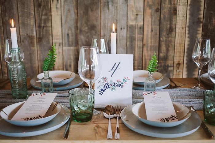 idée déco mariage simple rustique, table en bois brut, bouteilles en verre avec des bougies, fioles avec des brins de feuilles, chemin de table gris