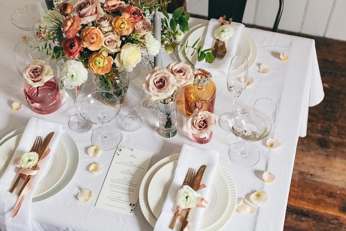 deco mariage pas cher, fleurs arrangées dans des talles, bouteilles et bocaux colorés et pétales de roses dispersées sur al table, serviette blanche et couverts décorés de fleur et ruban rose