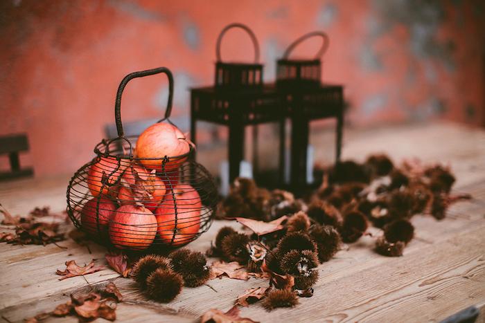 idée déco mariage automne, table en bois avec des glands, pommes, lanternes noires et feuilles mortes