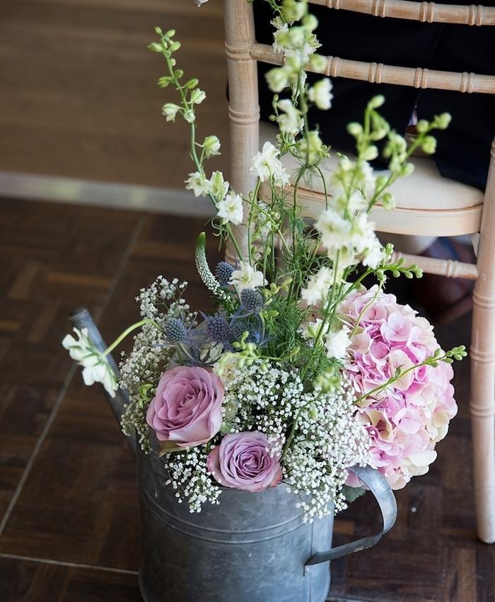 idee de deco mariage champetre, arrosoir vintage en zinc avec bouquet de fleurs dedans, derrière une chaise