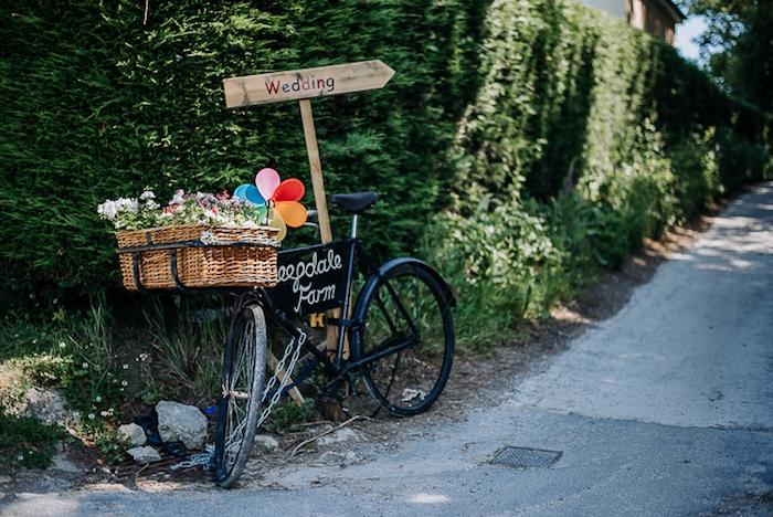 exemple de deco mariage champetre, velo noir avec panier, rempli de fleurs, ballons colorés et flèche mariage