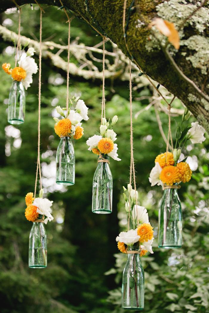 exemple de deco mariage pas cher, des bouteilles en verre avec des fleurs orange et blancs dedans, petits vases suspendus par des ficelles à une branche d arbre