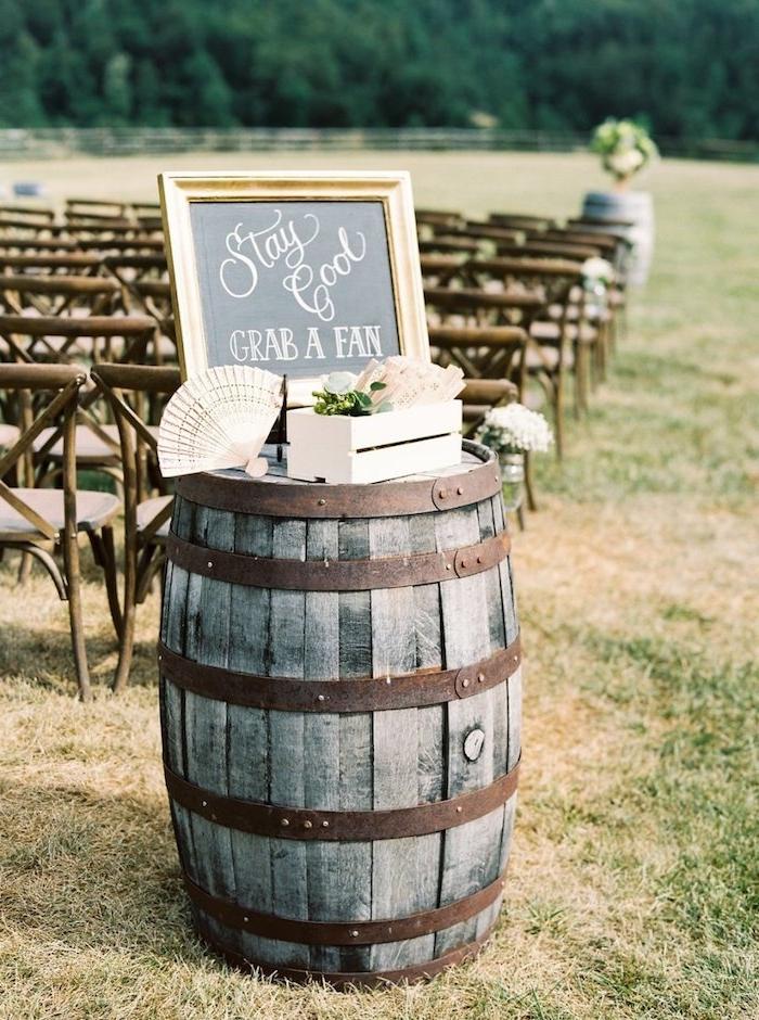 exemple de deco mariage champetre chic, tonneau en bois et metal avec un cagette en bois remplie d éventails pour les invités