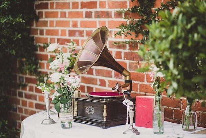 deco mariage vintage, gramophone retro, nappe blanche, vieux bouquin, bouteilles et pots en verres contenant des fleurs, fon de mur en briques