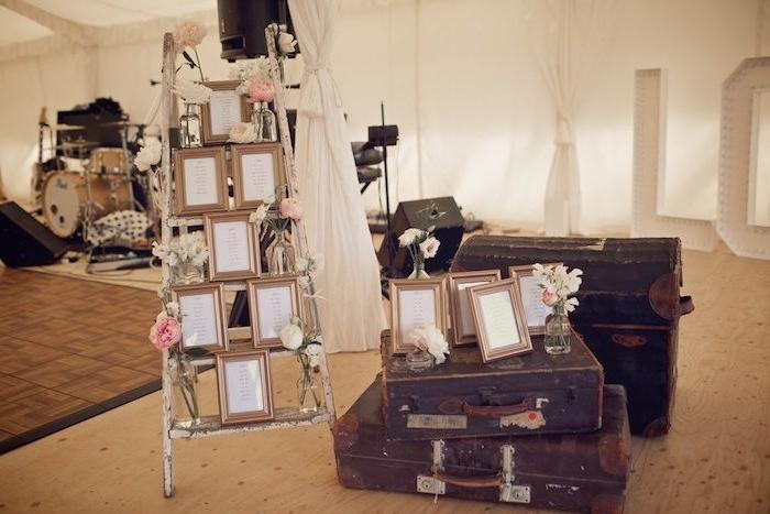 diy mariage avec escabeau récup, décoré de fleurs et des cadres photos avec les listes des invités, malles vintage usés