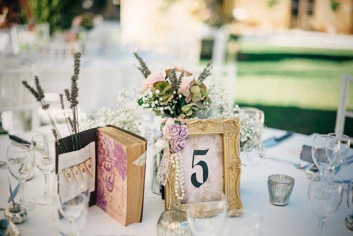deco mariage vintage champetre, table décoré de cadre vintage, fleurs, collier de perle, bouquin vintage, lavande