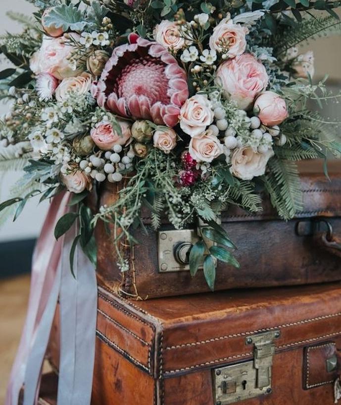 une pile de malles vintage en cuir aec un bouquet de fleurs en dessus et ruban rose, deco mariage vintage