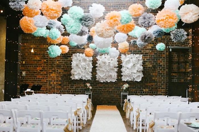 deco salle mariage, des fleurs en papier de soie colorées, couleur orange, bleu, blanc et gris, chaises blanches, mur en briques décorations blanches en papier