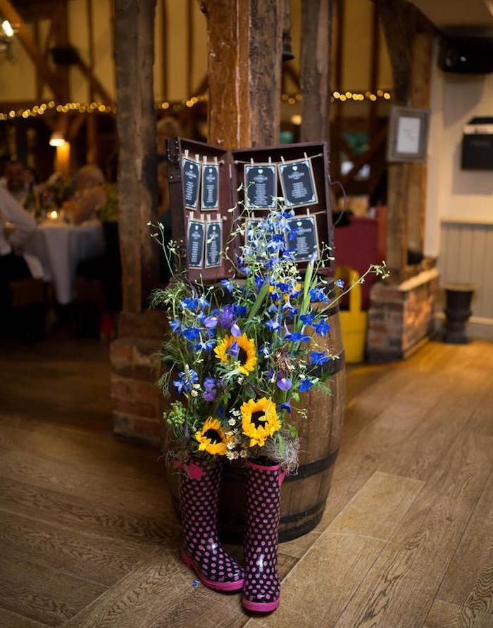deco mariage champetre, tonneau en bois, valise ouverte avec les listes invités suspendus à des ficelles, bottes remplis de fleurs champetre