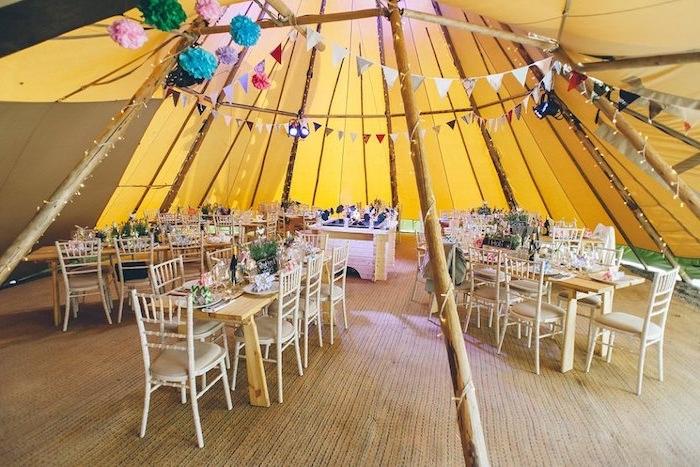 deco salle mariage avec des guirlande fanions colorées, fleurs en papier de soie, table et chases en bois, style rustique