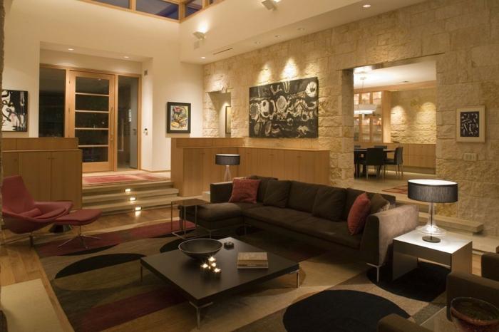 deco salon moderne, mur en pierre apparente, table carrée couleur foncée, éclairage doux, deux lampes à abat-jour