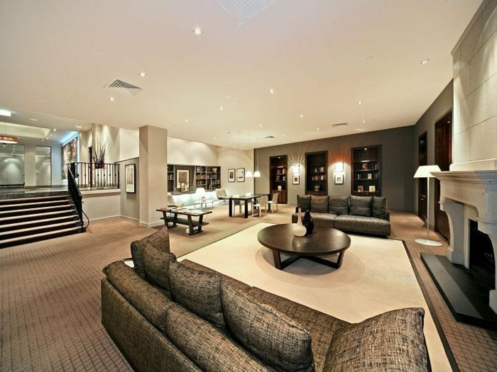deco salon moderne, salon moderne en gris et taupe, tapis couleur crème, table basse ronde, manteau de cheminée blanc
