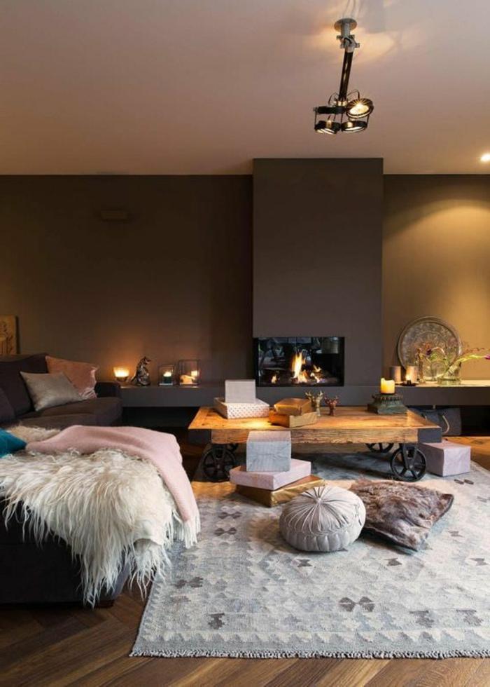 deco salon moderne, tapis gris, plaid cosy blanc, table basse sur roues, cheminée murale, peinture murale grise, plafonnier industriel, coussins déco