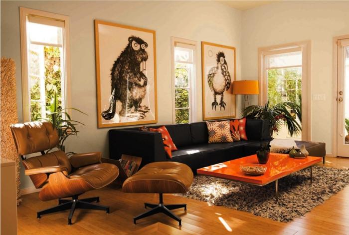 deco salon zen, petit tapis moelleux, sol en bois, peintures amusantes, table basse orange, canapé noir