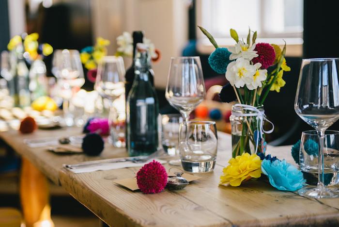 decoration table mariage en bois brut style campagne chic, pompons colorés, fleurs en tissu, pots en verre avec des fleurs dedans