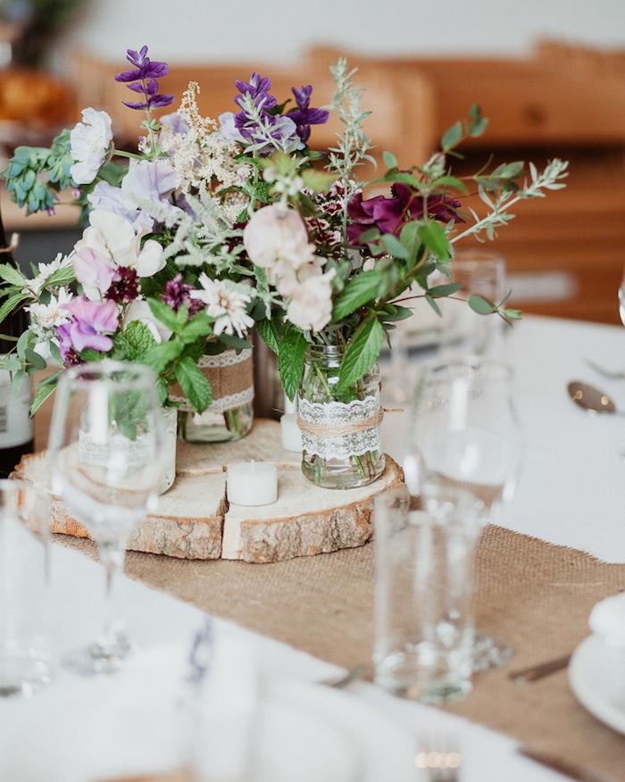 decoration table mariage avec chemin de table en toile de jute, rondelle en bois avec des pots en verre avec des bouquets de fleurs et déco en dentelle, jute et ficelle