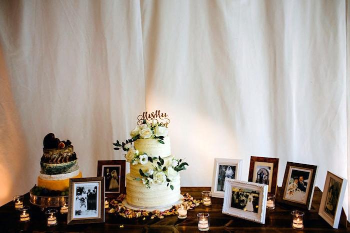 deco table mariage, gâteau entouré de décorations, bougies, pétales de fleurs, cadres photos couple, ancêtres