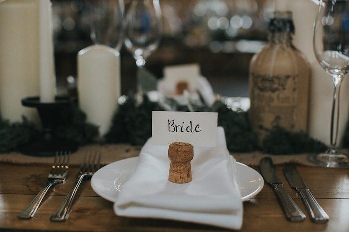 decoration table mariage, serviette blanche, bouchon de liège avec carton nom invité, table en bois rustique, bougies, bouteille, guirlande deco