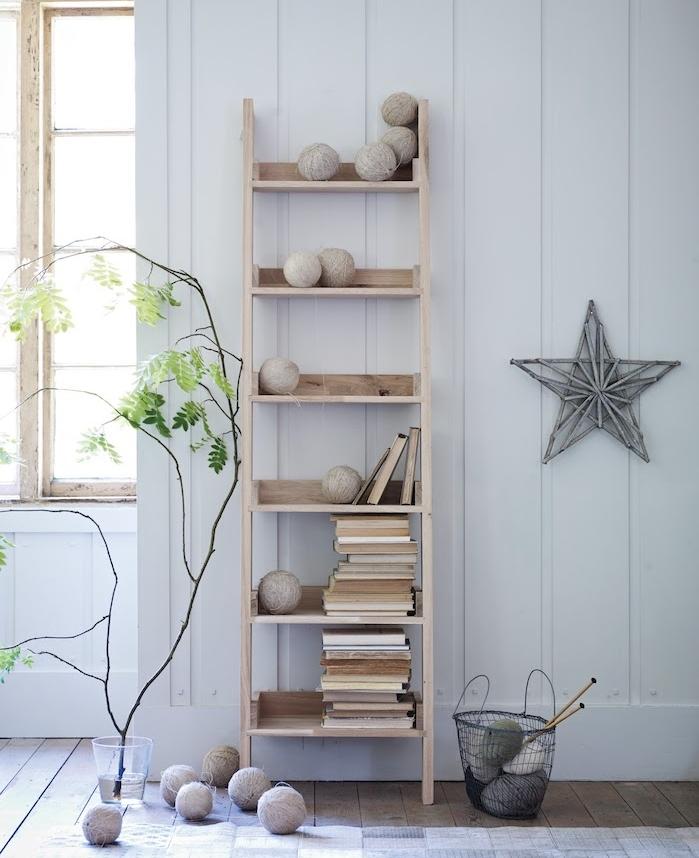 deco scandinave dans un salon, echelle decorative en bois, marches rangement pour livres, boules de laine, étoile décorative en branches de bois