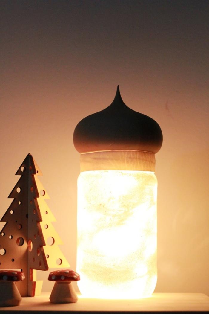 un luminaire fait maison fabriqué à partir d'un bocal en verre recyclé habillé de tissu et d'un couvercle en bois naturel