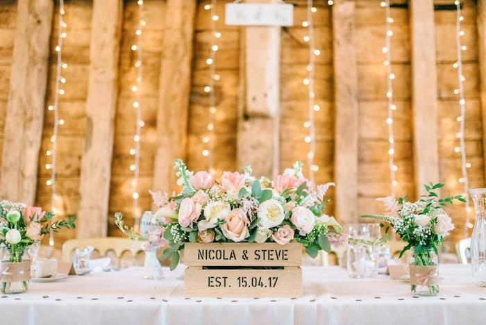 deco table mariage, cagette en bois fleurie avec des fleurs rose et crème, pots en verre transformés en vases, décorés de bandes de jute et ruban rose, guirlande lumineuse
