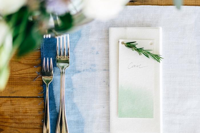 deco table mariage, couverts simple, marque place originale facile à créer, étiquette blanc et vert, brin de pin, sous assiette bleue t blanc