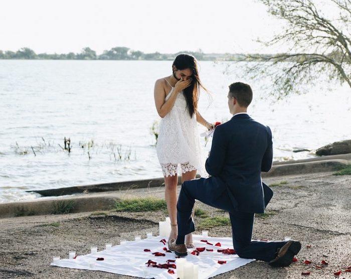 demande de fiancaille au bord d une rivière, une couverture blanche, pétales de rose, bougies, femme robe blanche et homme en costume