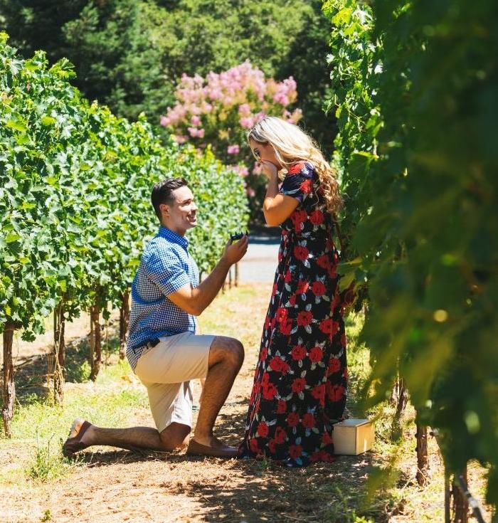 demande en mariage originale au milieu d un vignoble, grand jardin, home sur ses jambes et femme en robe d été