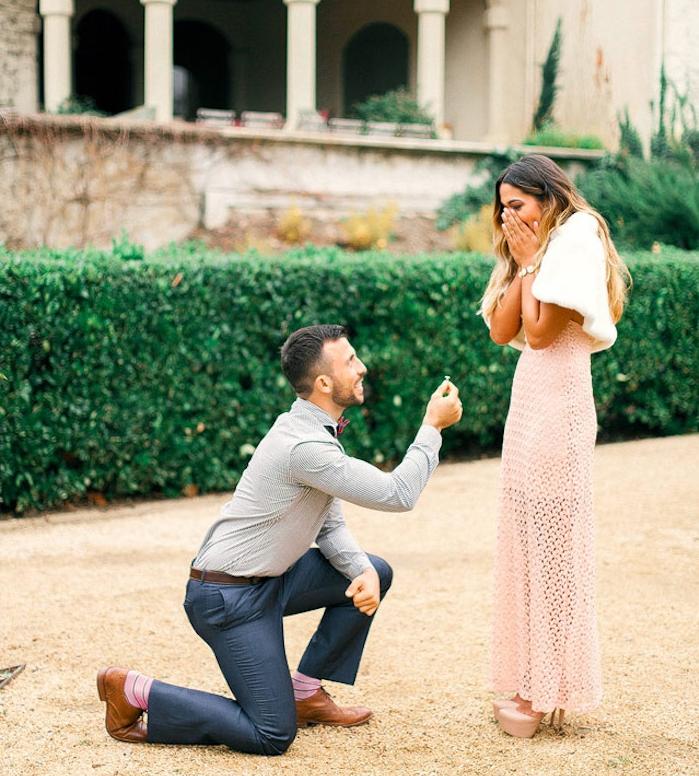 idée surprise mariage au milieu de la cour d un château, buis et bâtiment antique sur le fond, femme en robe rose et homme sur ses jambes