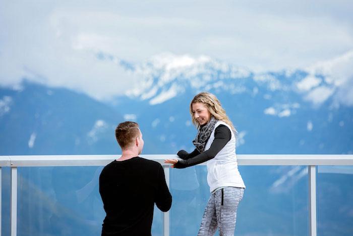 une idée de demande en fiancaille en hiver, une vue panoramique sur une montagne enneigée, jeune femme et homme