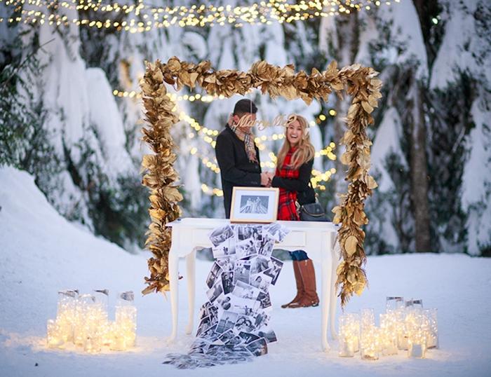 demande en mariage romantique en hiver, au milieu du forêt enneigé, table blanche, guirlande de feuilles dorées, lanternes avec des guirlandes lumineuses et pele mele de photos couple