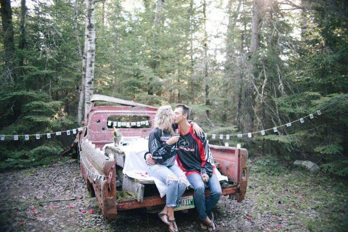 une camionnette décorée de couverture blanche et photos, homme et femme look rock, champagne, demande de fiancaille