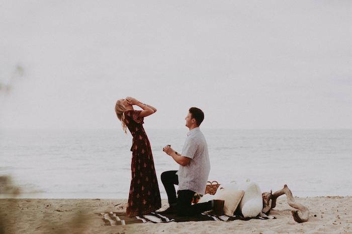 demande en mariage originale, plage ensablée, pique nique romantique, couverture blanc et marron, coussins décoratifs