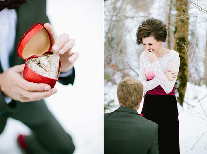 demande en mariage originale, conte d hiver dans un forêt, homme costume et femme robe blanc et rouge, boite bague en forme de coeur rouge