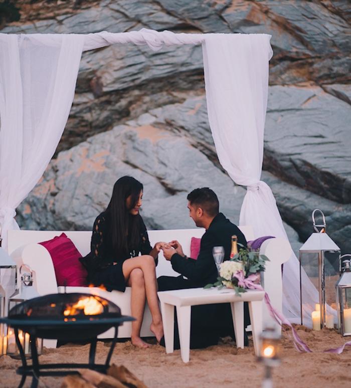 demande en mariage romantique sur la plage, sable doré, brasero, grandes lanternes, canapé blanc et voile blanche, coussins framboise, bouquet de fleurs